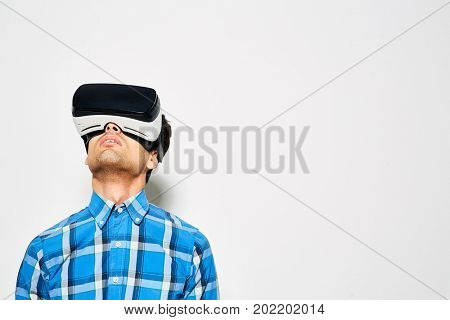Concentrated young man looking upwards while playing game with help of VR headset, studio shot
