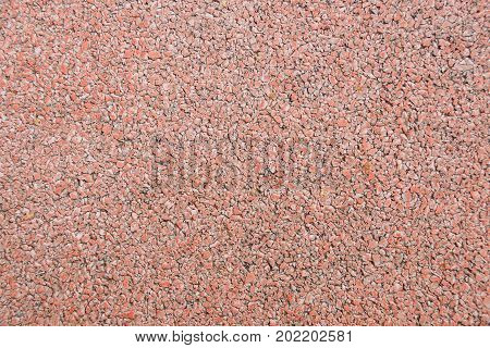 Seamless texture of a coating of crumbs of red decorative stones