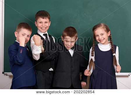 group pupil as a gang, posing near blank chalkboard background, grimacing and emotions, friendship and education concept