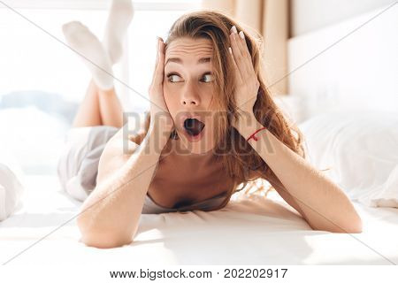 Shocked young woman in pajamas lying in bed and looking aside with opened mouth