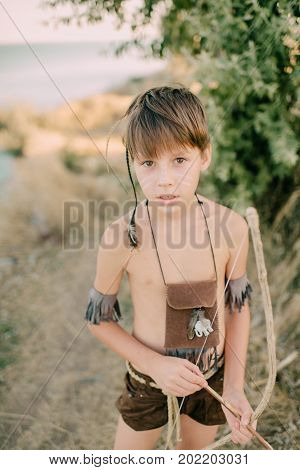 Boy playing in the indian on the seashore