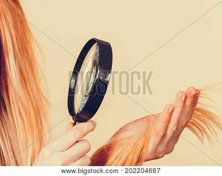 Haircare health problem concept. Unhappy blonde woman looking at ends of her blonde hair through magnifying glass