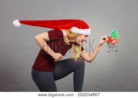 Xmas seasonal sales winter celebration concept. Happy woman wearing Santa Claus helper hat holding shopping basket cart with little christmas tree and gifts inside running for sale.