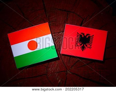 Niger Flag With Albanian Flag On A Tree Stump Isolated