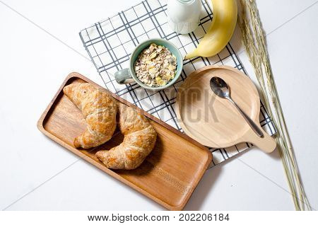 Breakfast with Croissant and Muesli and banana and fresh milk in white background