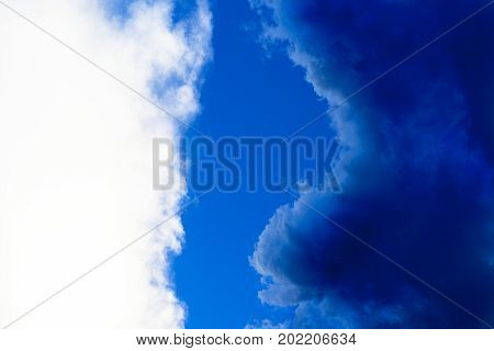 Contrast Between White And Dark Blue Clouds In A Clear Blue Sky