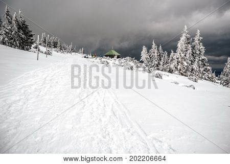 winter on Jeleni studanka in Jeseniky mountains in Czech republic with snow tress stone hut and clouds
