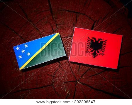 Solomon Islands Flag With Albanian Flag On A Tree Stump Isolated