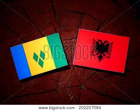 Saint Vincent And The Grenadines Flag With Albanian Flag On A Tree Stump Isolated