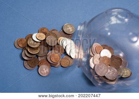 Glass Jar With Money, Coins Spilled From A Piggy Bank,