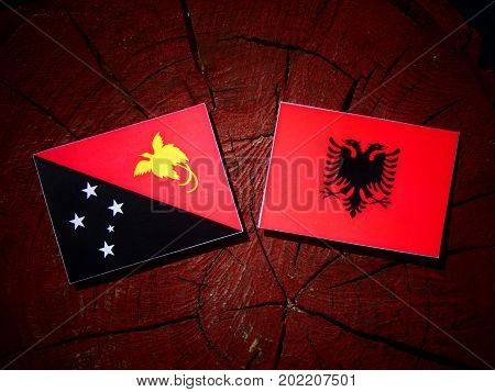 Papua New Guinea Flag With Albanian Flag On A Tree Stump Isolated