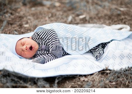 Yawning newborn baby lies on blue coverlet in grass.