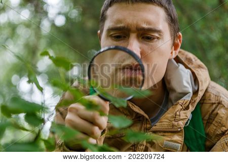 Portrait of young botanist with magnifying glass in forest on summer day