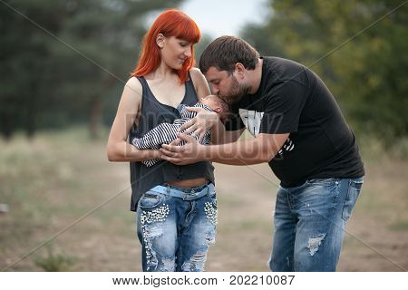 Happy young family with newborn baby on walk in park. Mother holds in her hands newborn baby father stands near and kisses his baby.
