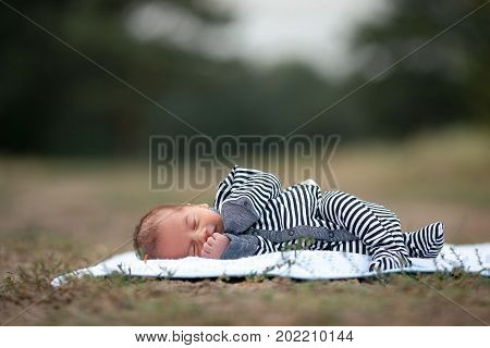 Newborn baby in stripy romper sleeps on blue coverlet on grass in park. Copy space top.
