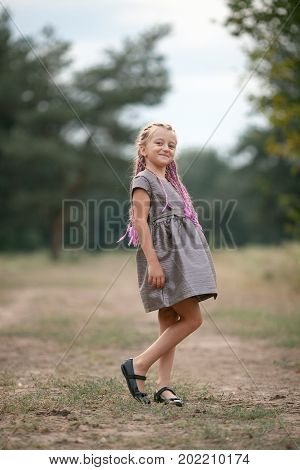 Happy child girl with pigtails stands on walk in park.