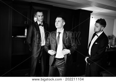 Handsome Groom Posing With His Groomsmen In The Room Before A Wedding. Black And White Photo.