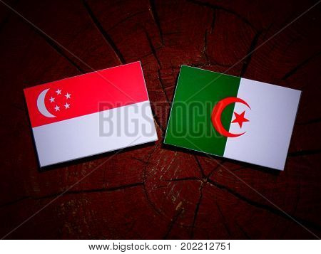 Singaporean Flag With Algerian Flag On A Tree Stump Isolated