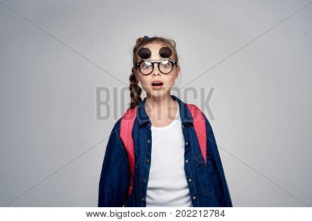 little girl on a light gray background with glasses.