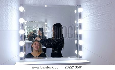 Professional hairdresser doing hairstyle for young pretty woman with long hair in white make up room. Beauty and haircare concept