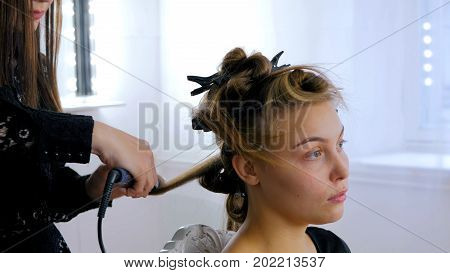 Professional hairdresser, stylist making curls for woman in white make up room. Beauty and haircare concept