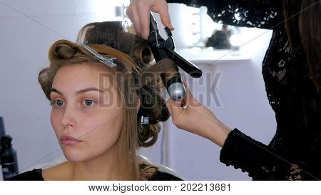 Professional hairdresser, stylist combing hair of female client and making curls in white make up room. Beauty and haircare concept
