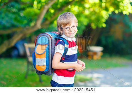 Beautiful happy little kid boy with glasses and backpack or satchel on his first day to school or nursery. Child outdoors on warm sunny day, Back to school concept