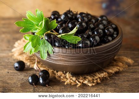 Fresh Berries Of Golden Currant In Ceramic Bowl On Wooden Background