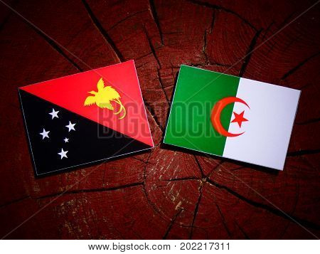 Papua New Guinea Flag With Algerian Flag On A Tree Stump Isolated