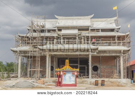 Construction worker working on a construction site of Chinese joss house in Thailand