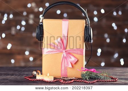 Beautiful composition with gift box and headphones on table against blurred lights. Christmas music concept