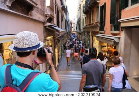 Young photographer takes a picture to people walking in the pedestrian zone