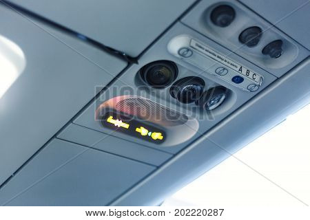 airplane cabin interior detail. No smoking and seat belt signal
