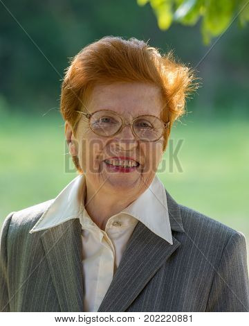 Portrait of cheerful woman in aged park. Age eighty years. A woman in a business suit.