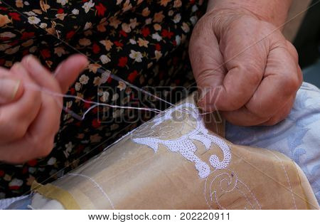 Hands Of An Elderly Woman Embroidering A Lace With Tombolo And C