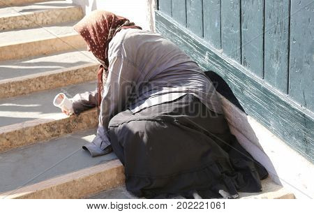 Gypsy Woman With Headscarf And Long Skirt Begging People