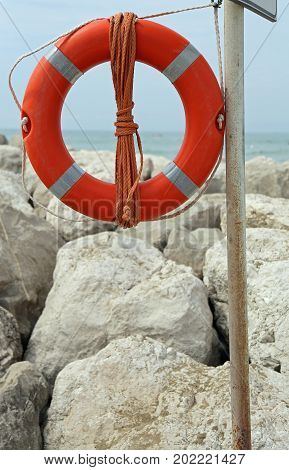 Big Red Buoy On The Rocks To Help Swimmers