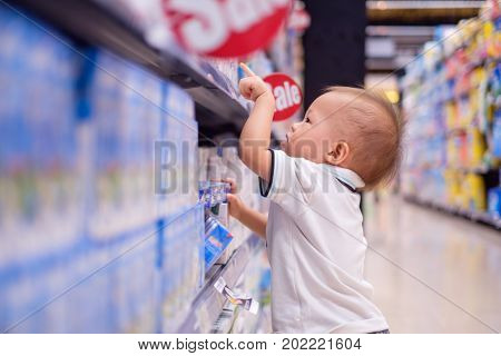 Cute little Asian 18 months / 1 year old toddler baby boy child standing and choosing milk product in grocery store / department store kid purchasing milk in shop