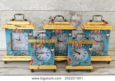 A group of handmade clocks decoupaged in a vintage shabby chic style and gilded with gold leaf