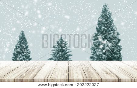 Christmas And New Year Background. Wooden Table Top With Blur Christmas Tree Pine Or Fir In Snowfall