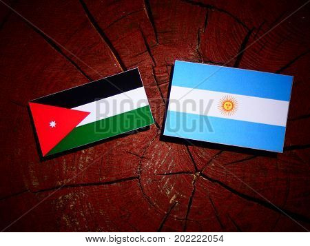 Jordanian Flag With Argentinian Flag On A Tree Stump Isolated
