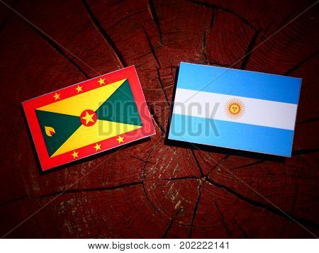 Grenada Flag With Argentinian Flag On A Tree Stump Isolated