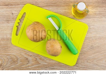Raw Unpeeled Potatoes, Vegetable Peeler On Cutting Board And Oil