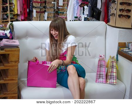 A close-up portrait of a sitting young woman on a white sofa background. A stylish female on sofa looking on on her purchases in a clothing store. Shopping, consumerism concept. Copy space.
