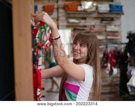A rich female choosing herself a beautiful stylish dress in a clothing store. A close-up portrait of a smiling woman on a blurred background. Shopping, consumerism concept. Copy space.