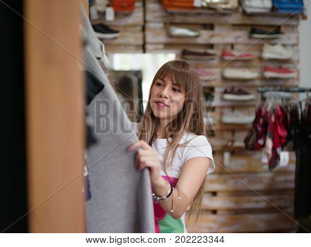 A portrait of a young woman on a blurred background, close-up. A beautiful lady choosing herself a beautiful stylish dress in a clothing store. Shopping, consumerism concept. Copy space.