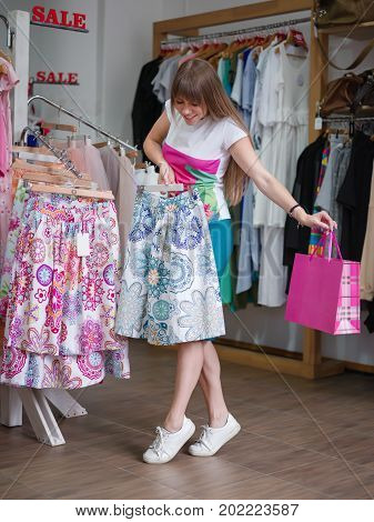A full-length portrait of a young woman on a blurred background. A female choosing herself a beautiful colorful fashionable skirt in a clothing store. Shopping, consumerism concept. Copy space.