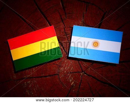 Bolivian Flag With Argentinian Flag On A Tree Stump Isolated