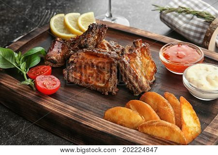 Wooden tray with delicious ribs and vegetables, closeup