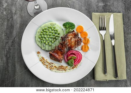 Plate with delicious ribs, vegetables and mushy peas on table